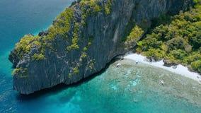 Visión aérea sobre el arrecife de coral y los barcos turísticos del banca en la playa de Entalula, bahía de Bacuit, EL-Nido Isla  almacen de video