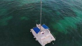 Visión aérea sobre el mar del Caribe Catamarán o velero en el agua en la salida del sol metrajes