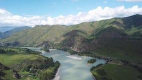 Visión aérea sobre el río Katun de la turquesa entre los árboles y los prados en las montañas del Altai debajo de nubes blancas y metrajes