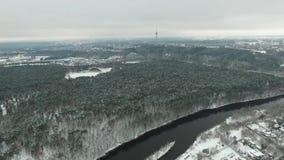 Visión aérea sobre la ciudad cerca del invierno del río y del bosque almacen de video