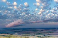 Visión aérea sobre una escena rural hermosa con los campos y árboles verdes y nubes blancas y rosadas hermosas foto de archivo libre de regalías