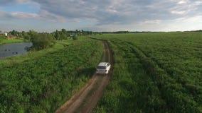 Visión aérea trasera: SUV de plata grande que conduce en campo verde en el camino almacen de video