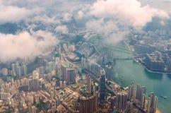 Visión aérea a través de las nubes a una ciudad grande de la metrópoli de Hong Kong foto de archivo libre de regalías