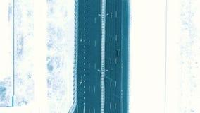 Visión aérea verticalmente abajo de la carretera en el invierno en nevadas, conducción de automóviles en la carretera almacen de video
