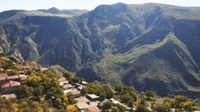 Visión aérea: Vuelo sobre pueblo de montaña del otoño dentro de la luz suave de la salida del sol del forestin Paisaje hermoso almacen de video