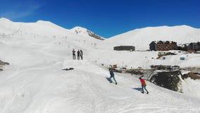 Visión alrededor de la cuesta del esquí con la gente en ella, montañas almacen de metraje de vídeo