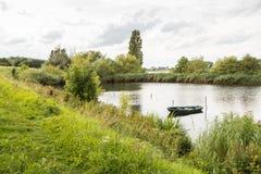 Visión con un pequeño barco de rowing en el agua Foto de archivo