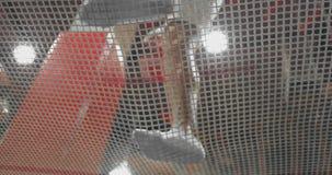 Visión de debajo a través de la malla de los acróbatas del trampolín que saltan en un trampolín Vuelo y tirones almacen de video
