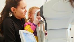 Visión del control del niño usando el aparato oftálmico Imagen de archivo libre de regalías