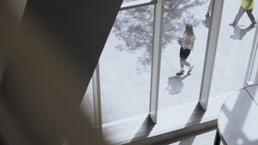 Visión dentro del edificio Mujer hermosa joven que camina cerca de la ventana en oficina para trabajar en día soleado, usando sma metrajes