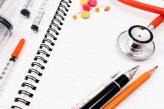Visión desde arriba Accesorios médicos con el cuaderno en blanco Foto de archivo