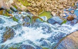 Visión desde arriba de la cascada que cae abajo, paisaje del bosque con una cascada, donde comienza la pendiente para regar Foto de archivo libre de regalías