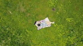 Visión desde arriba de la mujer joven que miente en hierba y que usa el cuaderno metrajes