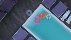 Visión desde arriba de la piscina con los círculos inflables coloreados brillantes Una vista superior de la piscina con multicolo almacen de metraje de vídeo