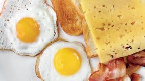 Visión desde arriba de tostadas fritas sabrosas frescas con queso y el huevo el freír con tocino en la placa almacen de metraje de vídeo