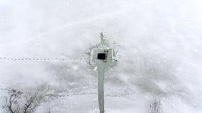 Visión desde arriba en el hielo-agujero ajustado con camino de la orilla y las huellas humanas en el hielo del lago del invierno  imagenes de archivo