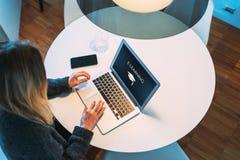 Visión desde arriba La muchacha del estudiante se está sentando en la tabla blanca redonda y utiliza el ordenador portátil con un imagenes de archivo