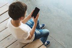 Visión desde arriba Muchacho en sentarse blanco de la camiseta y de las gafas de sol interior y smartphone de las aplicaciones El Imagen de archivo libre de regalías
