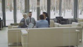 Visión desde bajar el elevador al grupo de hombres de negocios de los colegas que discuten las cartas financieras que asisten en  almacen de metraje de vídeo