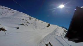 Visión desde de arriba a abajo en cuesta nevada del esquí y rastros de la elevación de silla opinión de la Primero-persona almacen de video