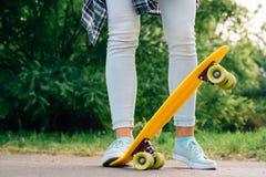 Visión desde detrás de la muchacha en vaqueros, camiseta y las zapatillas de deporte, que Fotos de archivo libres de regalías