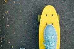 Visión desde detrás de la muchacha en vaqueros, camiseta y las zapatillas de deporte, que Imagen de archivo