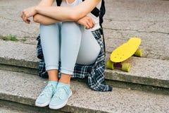 Visión desde detrás de la muchacha en vaqueros, camiseta y las zapatillas de deporte, que Imagenes de archivo