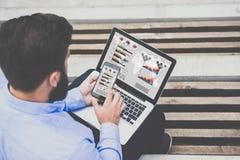 Visión desde detrás de sentarse barbudo joven del hombre de negocios exterior y del trabajo en el ordenador portátil con los gráf Imagen de archivo