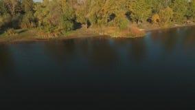 Visión desde el abave del pescador con una caña de pescar en la orilla del río Tiroteo del abejón metrajes