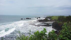 Visión desde el acantilado de la costa costa con las ondas que caen en orillas en día de verano ventoso almacen de metraje de vídeo