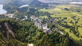 Visión desde el aire al castillo del castillo de Neuschwanstein en las montañas alpinas Imagen de archivo
