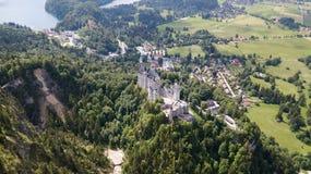 Visión desde el aire al castillo del castillo de Neuschwanstein en las montañas alpinas Foto de archivo libre de regalías