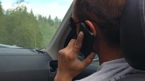Visión desde el asiento trasero de un coche en un hombre joven que habla en un teléfono móvil almacen de metraje de vídeo
