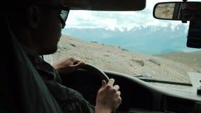 Visión desde el coche de SUV dentro con la parte del interior y el espejo con la mano masculina del conductor en el volante en pe