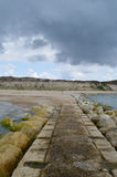 Visión desde el embarcadero a la playa y a los acantilados con el cielo azul y las nubes tempestuosas Fotos de archivo