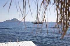 Visión desde el embarcadero a un velero que flota en el mar contra el th Imagen de archivo libre de regalías