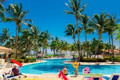 Visión desde el lado del pasillo del hotel en la invitación la piscina tropical del jardín con de la gente y de los niños que dis Foto de archivo