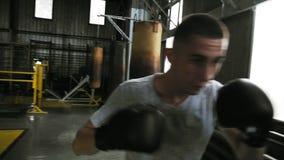 Visión desde el lado del saco de arena, cantidad de un boxeador de sexo masculino que se resuelve en el gimnasio en guantes negro almacen de metraje de vídeo