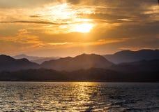 Visión desde el mar en la orilla distante con el ove del sol poniente Imagen de archivo libre de regalías