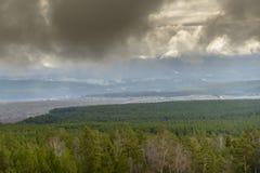 Visión desde el paso de montaña de la ciudad debajo de las nubes bajas Imagen de archivo