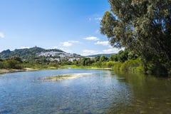 Visión desde el río de un pueblo de montaña con un castillo en el top Fotos de archivo
