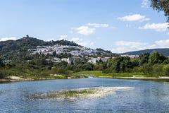 Visión desde el río de un pueblo de montaña con un castillo en el top Foto de archivo libre de regalías