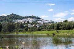 Visión desde el río de un pueblo de montaña con un castillo en el top Imágenes de archivo libres de regalías