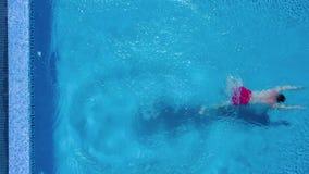 Visión desde el top como un hombre se coloca al borde de la piscina, de las zambullidas y de las nadadas debajo del agua metrajes