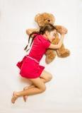 Visión desde el top de la muchacha que miente en piso y que duerme en oso de peluche Fotografía de archivo