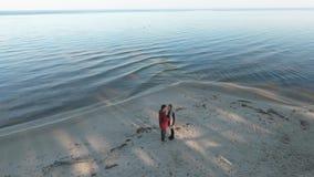 Visión desde el top en un par que camina a lo largo de la orilla del río arenosa Relación de los pares que pasan el tiempo junto almacen de metraje de vídeo