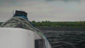 Visión desde el yate blanco de lado a la orilla enselvada y al cielo cubierto almacen de metraje de vídeo