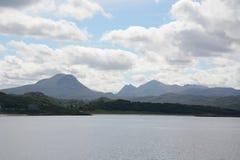 Visión desde Gairloch de la iglesia, de la playa y de montañas Imagenes de archivo