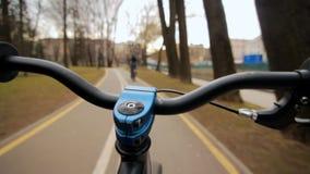 Visión desde la barra de la manija mientras que conduce Conducción de la bicicleta en el camino asfaltado del parque almacen de metraje de vídeo