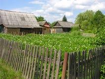 Visión desde la calle a través de una cerca en el edificio agrícola Fotos de archivo